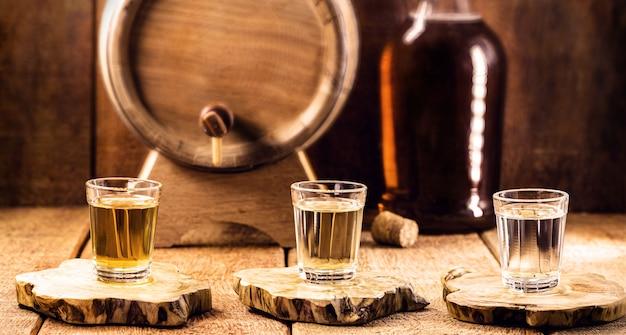 サトウキビで作られた「pinga」または「cachaã§a」と呼ばれる典型的なブラジルのブランデーガラス、素朴なまだ設定