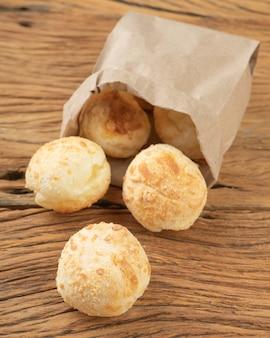 Типичные бразильские сырные булочки в бумажном пакете над деревянным столом.