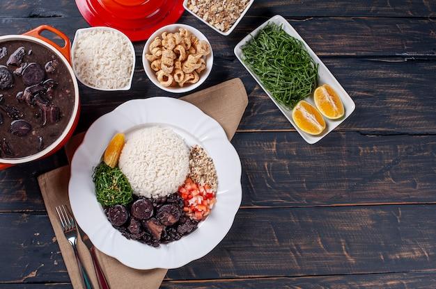 Типичное бразильское блюдо под названием фейжоада. сделано из черной фасоли, свинины и колбасы. вид сверху. копировать пространство
