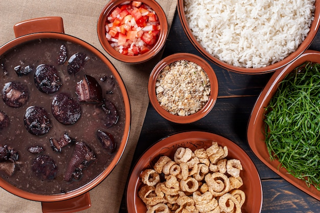 Типичное бразильское блюдо под названием фейжоада. сделано из черной фасоли, свинины и колбасы. вид сверху