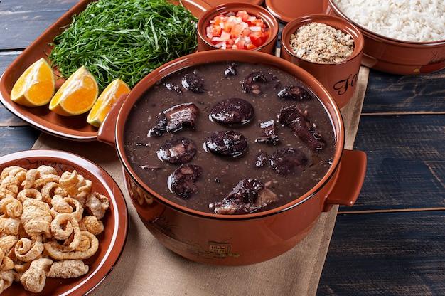 Типичное бразильское блюдо под названием фейжоада. сделано из черной фасоли, свинины и колбасы