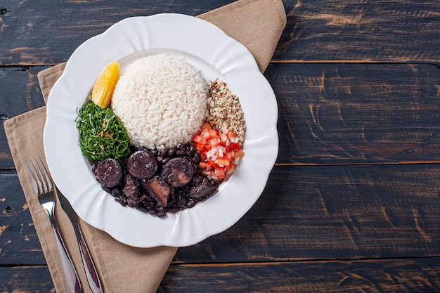 Typical brazilian dish called feijoada. made with black beans, pork and sausage. top view. copy space