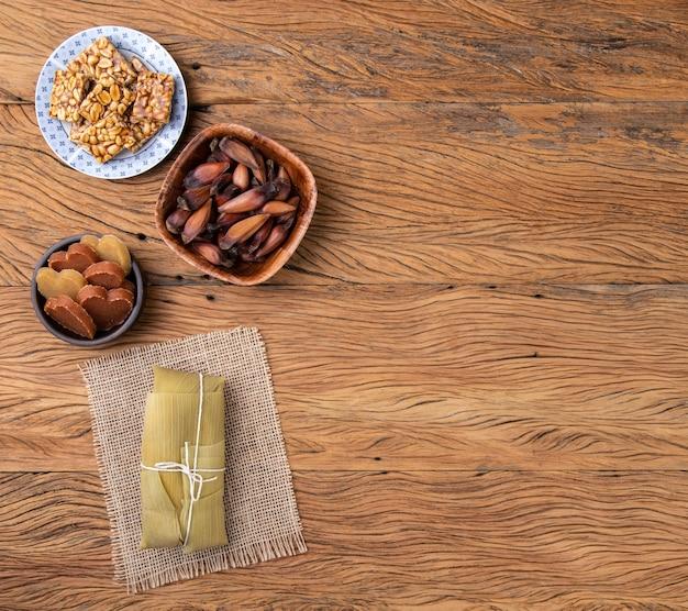 木製の背景の上面図に典型的なブラジルの6月のお祭りの食べ物