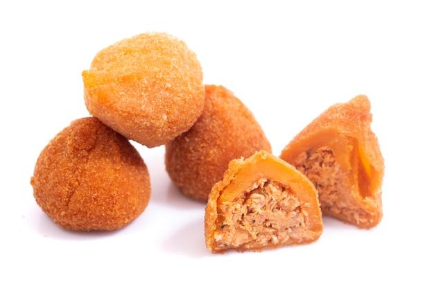 白い背景で隔離されたコシーニャデフランゴと呼ばれるブラジルからの典型的なフライドチキンの前菜。