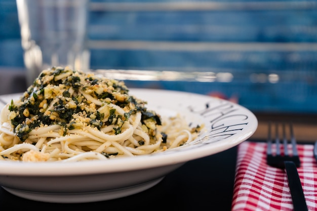 Typical dish of italian cuisine, spaghetti with genoese pesto sauce served in an allusive plate on a table with mediterranean colors. normal view. close plane.