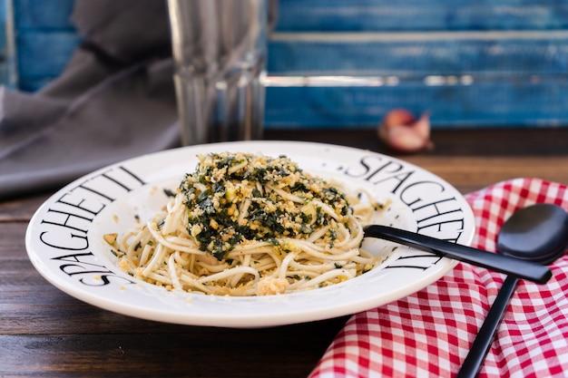 이탈리아 요리의 전형적인 요리인 제노바 페스토 소스를 곁들인 스파게티는 지중해 색상의 테이블에 암시적인 접시에 제공됩니다. 높은 시야, 중간 샷.