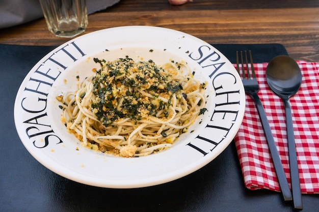 이탈리아 요리의 전형적인 요리인 제노바 페스토 소스를 곁들인 스파게티는 지중해 색상의 테이블에 암시적인 접시에 제공됩니다. 높은 전망,
