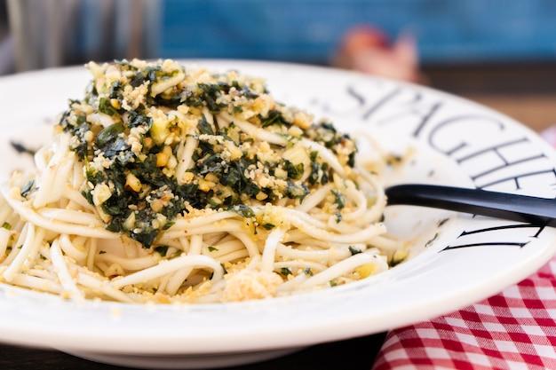 이탈리아 요리의 전형적인 요리인 제노바 페스토 소스를 곁들인 스파게티는 지중해 색상의 테이블에 암시적인 접시에 제공됩니다. 일반보기. 가까운 비행기. 파스타 한 입을 준비하는 사람.