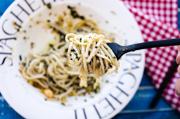 イタリア料理の典型的な料理、ジェノバのペストソースを添えたスパゲッティを地中海色のテーブルの上の魅力的なプレートで提供しています。上面図。パスタの一口のクローズアップ。