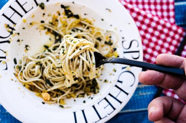 イタリア料理の典型的な料理、ジェノバのペストソースを添えたスパゲッティを地中海色のテーブルの上の魅力的なプレートで提供しています。上面図。パスタを一口食べるのを手伝っている人。