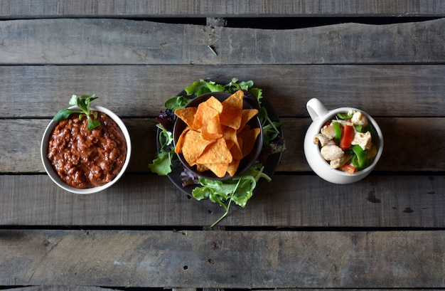 Typical dishes of mexico made guacamole, chili with meat, chicken, vegetables and nachos