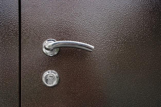 Typical door lock. doorknob. a metallic keyhole with knob on a brown metal door.