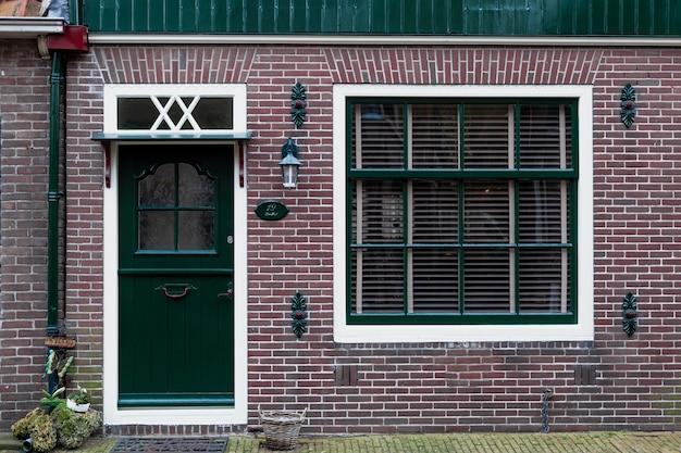 典型的なオランダの田舎の正面玄関と窓。ヴィンテージヨーロッパの村の家のファサード。美しいレトロな玄関ドアオランダ。
