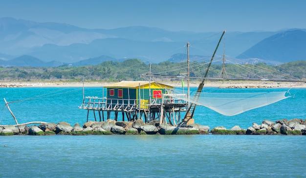 Типичная рыболовная сеть и рыбацкий домик с видом на море в марина ди пиза, тоскана, италия