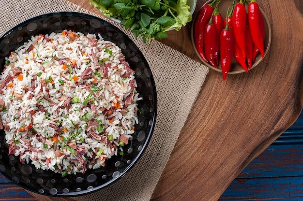 Типичная еда из южной бразилии, приготовленная из риса, сушеного мяса, колбасы пепперони, бекона и моркови.