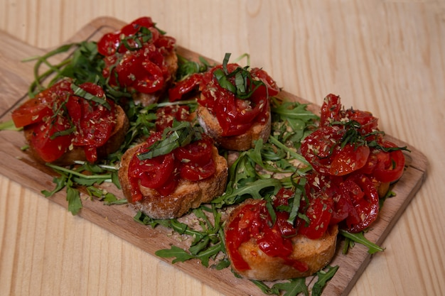Typical fresh neapolitan bruschettas with arugula on wooden board
