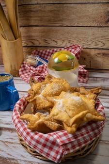 오래된 나무 테이블에 클래식 메이트와 함께 쟁반에 전형적인 튀긴 고구마와 마르멜로 페이스트리. 민족 또는 지역 요리 개념. 수직 방향.