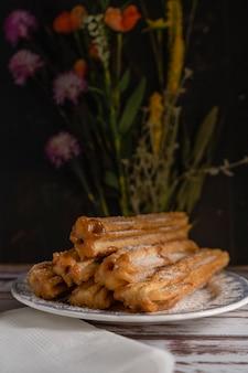 전형적인 히스패닉 츄로스는 오래된 판자에 있는 빈티지 접시에 덜체 드 레체로 가득합니다. 수직 프레임, 복사 공간.