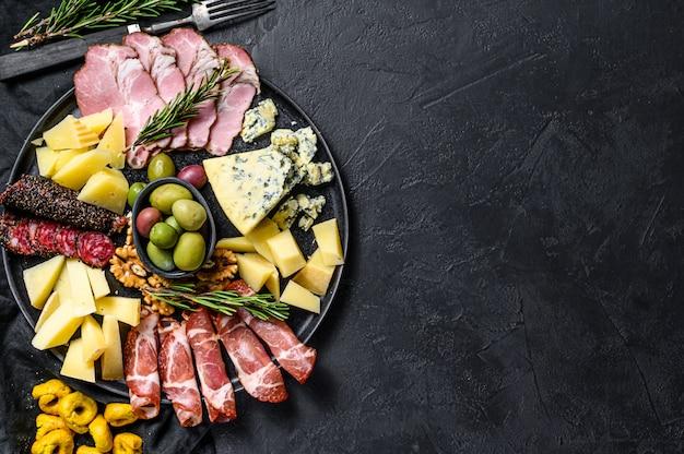 Типичный итальянский антипасто с ветчиной, ветчиной, сыром и оливками. черный фон. вид сверху. пространство для текста
