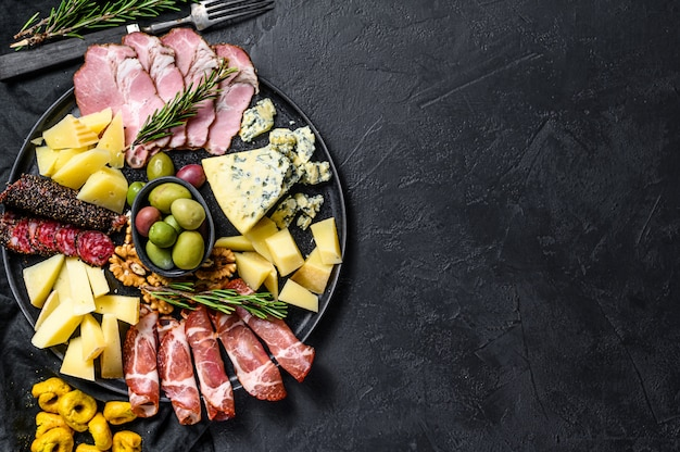 Typical italian antipasto with prosciutto, ham, cheese and olives. black background. top view. space for text