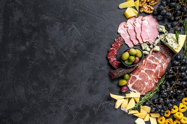 Typical italian antipasto with prosciutto, ham, cheese and olives. black wall. top view. space for text