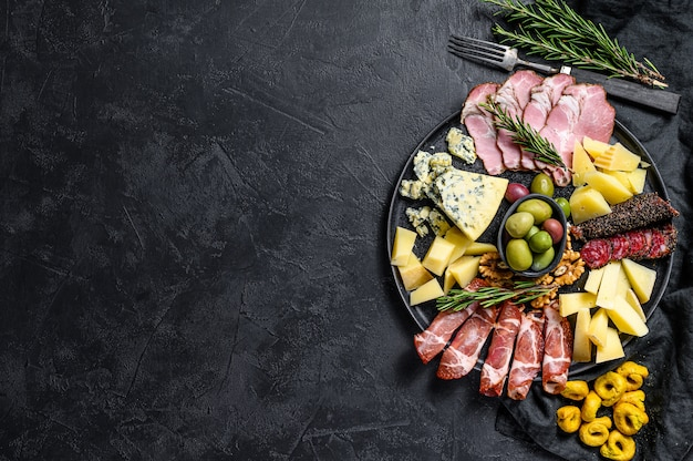 Typical italian antipasto with prosciutto, ham, cheese and olives. top view. copyspace background
