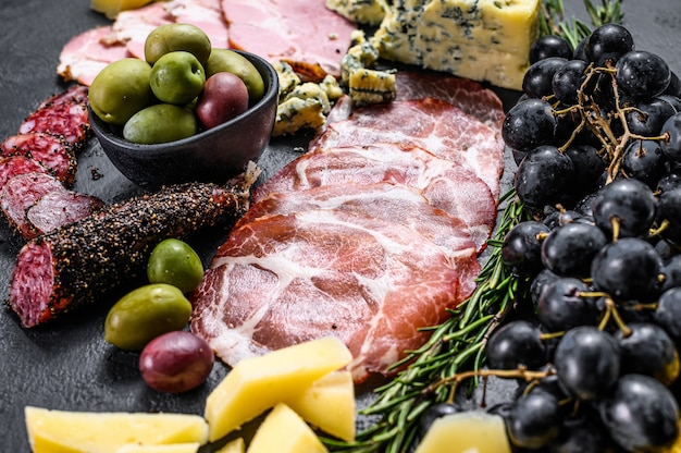Typical italian antipasto with prosciutto, ham, cheese and olives. top view