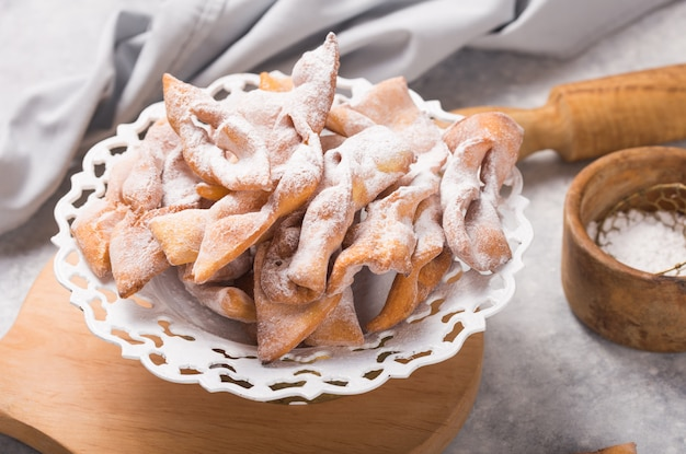 Typical italian carnival fritters dusted with powdered sugar on concrete table.