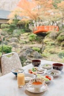 흰 돌과 녹색 식물이있는 일본 정원, 일본 요리가있는 전형적인 일본식 아침 식사