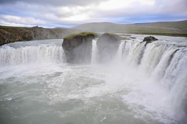 Типичные пейзажи в исландии. сверкающие айсберги и мощные водопады от тающего льда.