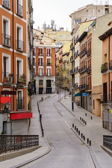 街の典型的な窓とバルコニーのある建物の間を曲がりくねった典型的なマドリッド通り。スペイン。