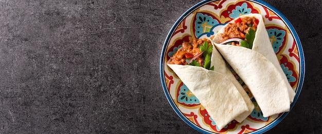 典型的なメキシコのブリトーラップ、黒のパノラマビューで牛肉、frijoles、野菜