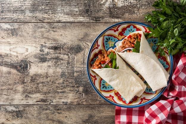 典型的なメキシコのブリトーラップ、木製のテーブルコピースペースで牛肉、フリジョーレ、野菜