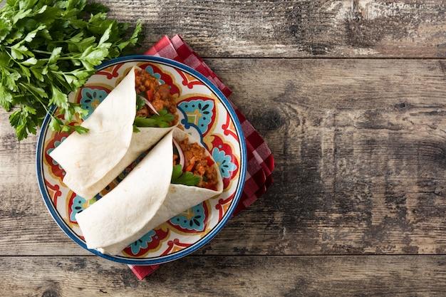 典型的なメキシコのブリトーラップ、牛肉、フリジョーレ、野菜の木製のテーブル