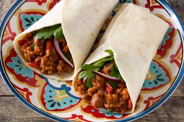 典型的なメキシコのブリトーラップ、牛肉、フリホレ、野菜、木製のテーブル