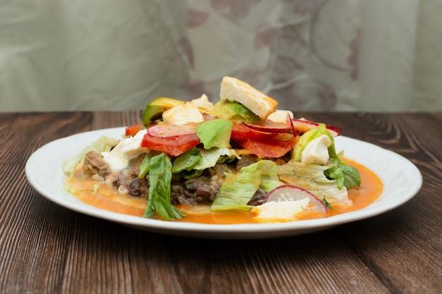 木製のテーブルの上の白いプレートのhuaracheと呼ばれる典型的なメキシコ料理