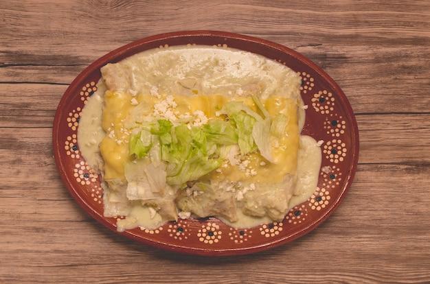 나무 테이블에 전형적인 멕시코 음식 녹색 엔칠라다