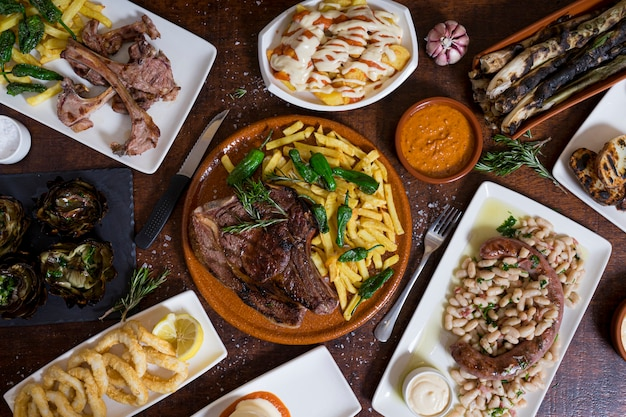 Typical mixed spanish dishes on dark brown wooden table. top view