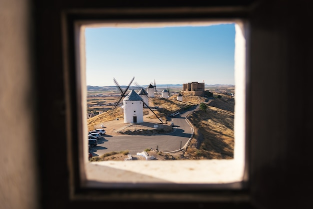 Typical old white windmill and medieval castle in spain seen from a window inside the mill