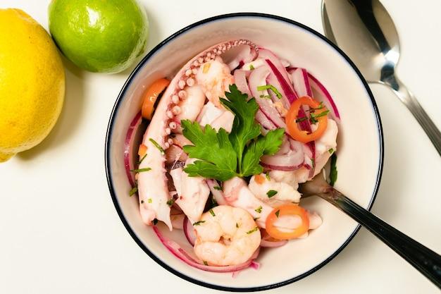 Типичная перуанская еда, севиче из кальмаров, креветки и белая рыба с фиолетовым луком и хорошее тигровое молоко. подается в белой миске. вид сверху.