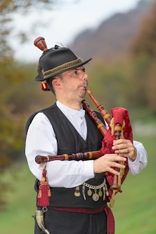 Typical player in traditional northern italy bagpipe costume, an alpine valley of bergamo