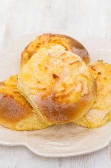 Typical portuguese buns with coconut on white plate