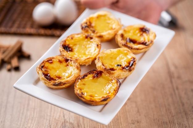 Типичные португальские пироги с заварным кремом. традиционная португальская выпечка. держит шеф-повар.