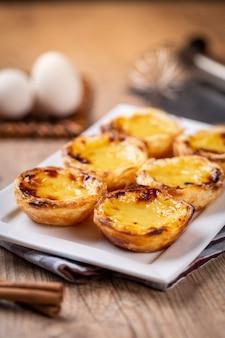 Типичные португальские пироги с заварным кремом. традиционная португальская выпечка. на деревянном столе.