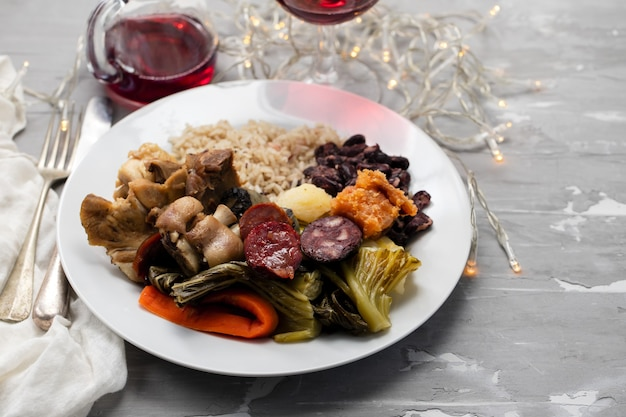 典型的なポルトガル料理の茹でた肉、燻製ソーセージ、野菜、白い皿にご飯