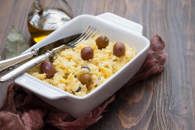Типичное португальское блюдо: яйца с треской и оливками в белом блюде bacalhau a lisbonense