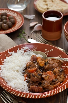 Typical portuguese dish feijoada with rice in ceramic bowl and red wine on brown wooden table