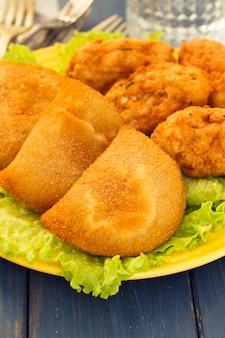 Typical portuguese snack ricoes de carne and bolinhos de bacalhau