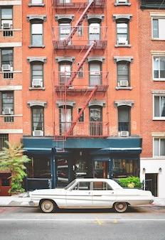 뉴욕의 화재 계단이있는 전형적인 붉은 벽돌 건물. 전경과 빈티지 사진 효과의 클래식 자동차.