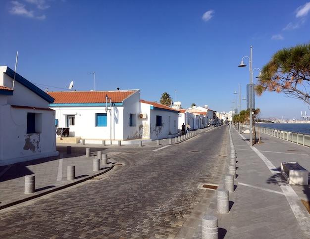 キプロスの典型的な南の海辺の街並み、冬のオフシーズンの明るい晴れた日に通りと白い家があります